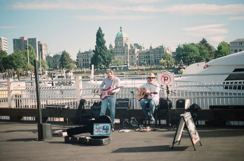 two men playing guitars on street