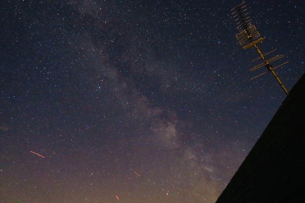 starry night sky over house with antenna