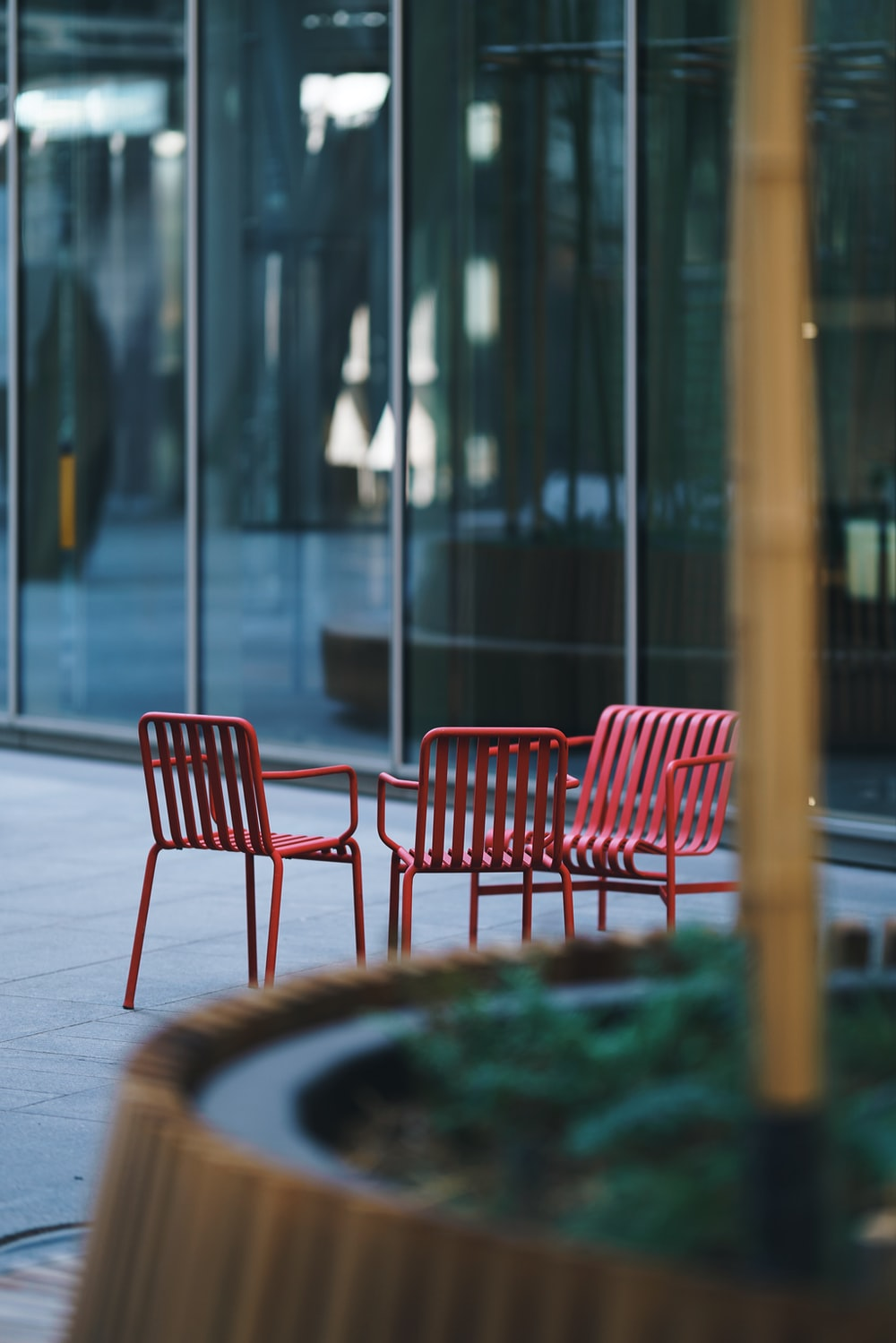 three red metal armchairs outside glass wall