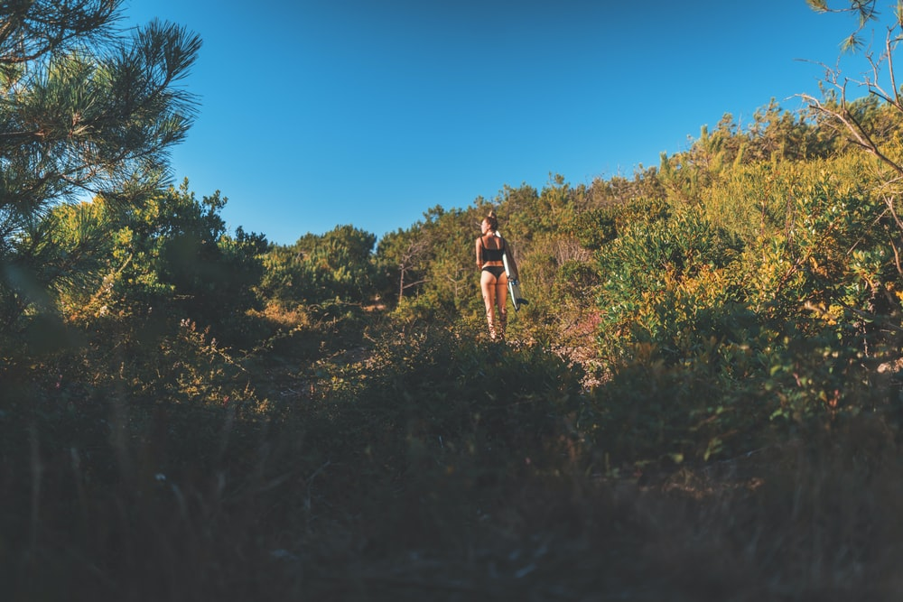 woman in black bikini standing on top of the hill