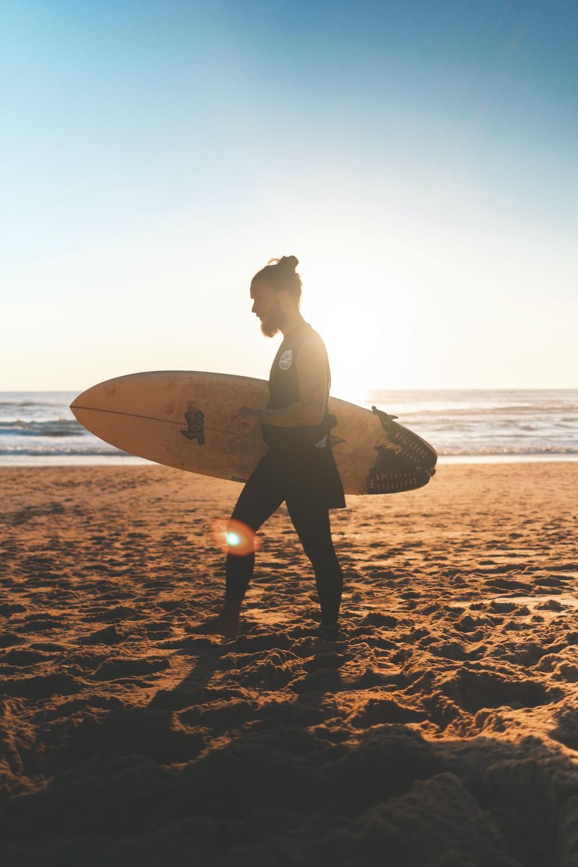 man walking on seashore with surfboard