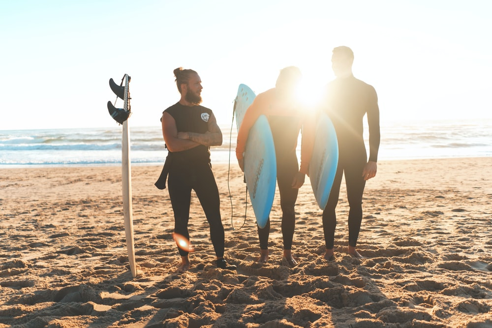 three men carrying surfboards standing on shore