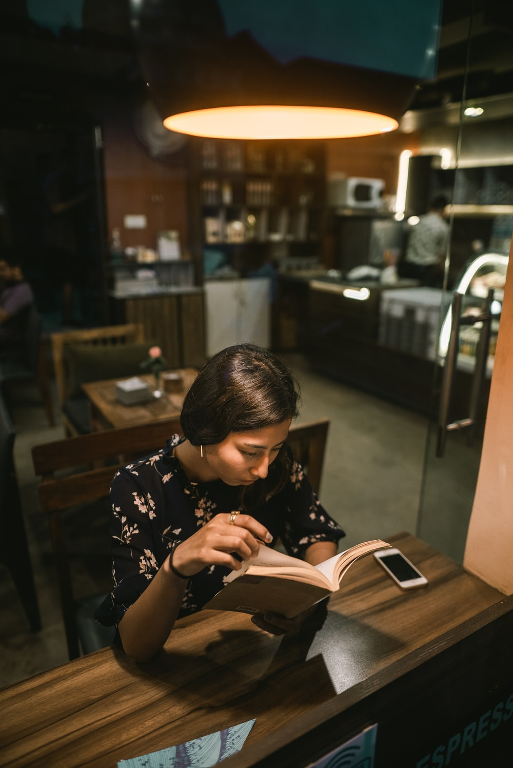woman reading book beside table