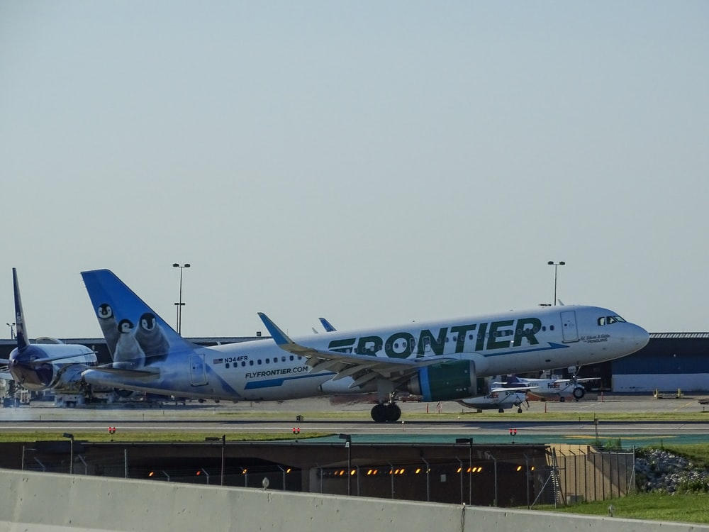 green and white Frontier airliner