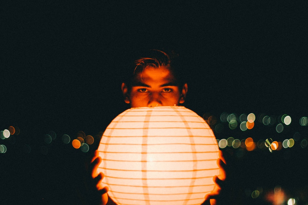 close-up photography of man holding lantern during nighttime
