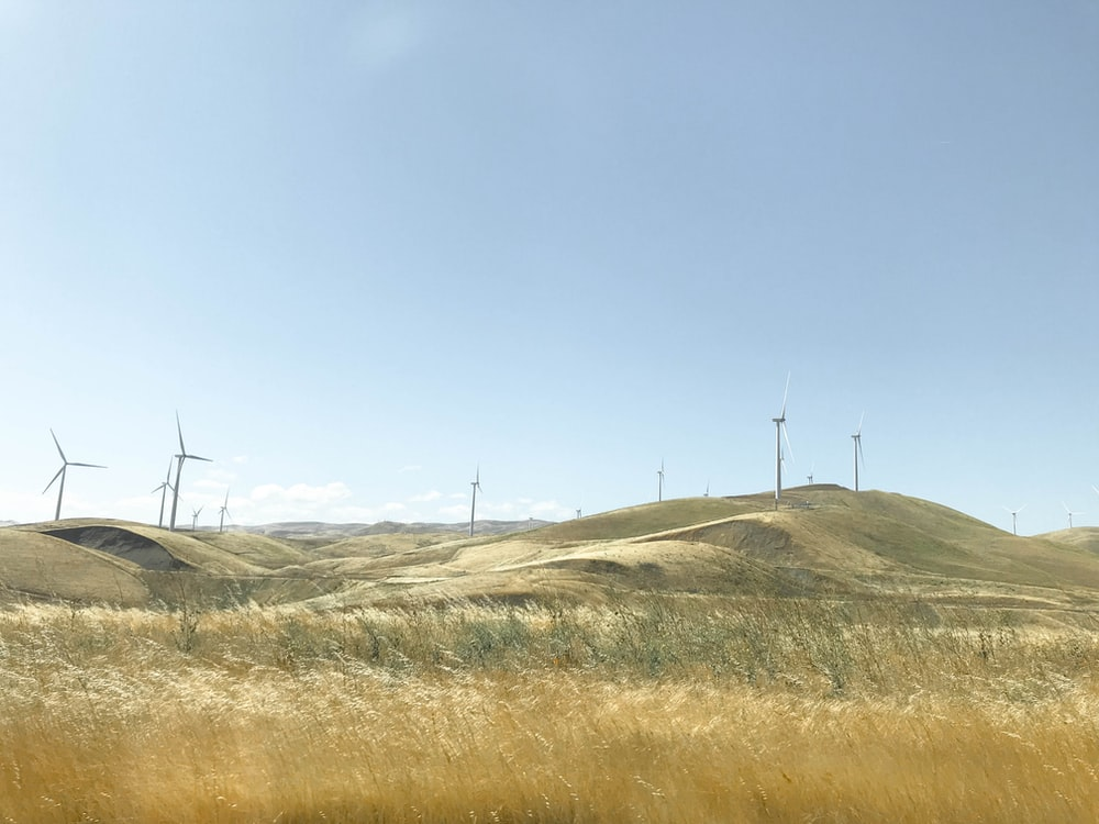 white wind mills on hill
