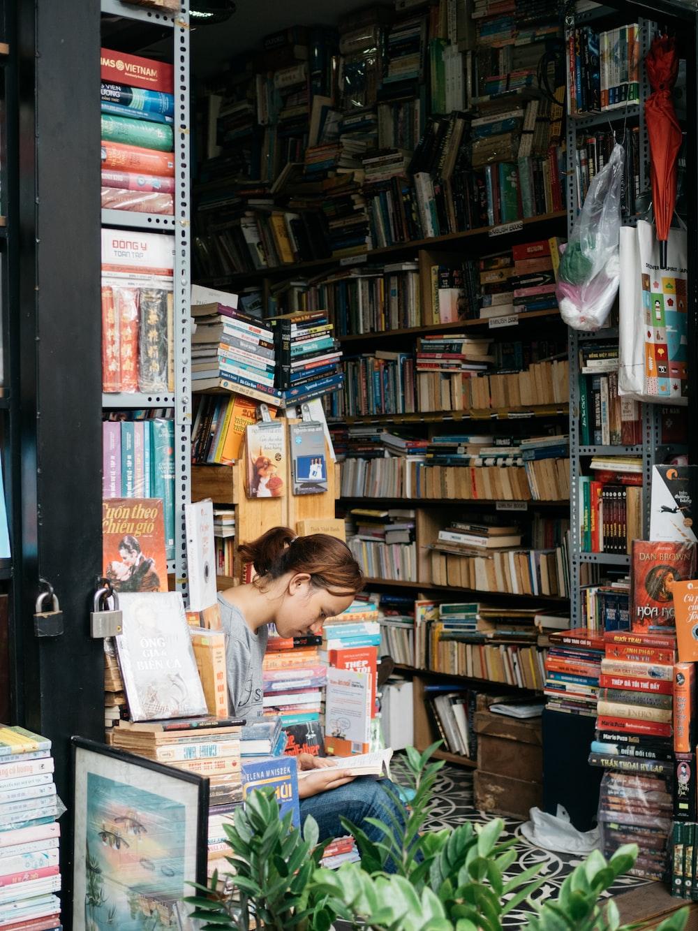 woman reading book in between books in shelf