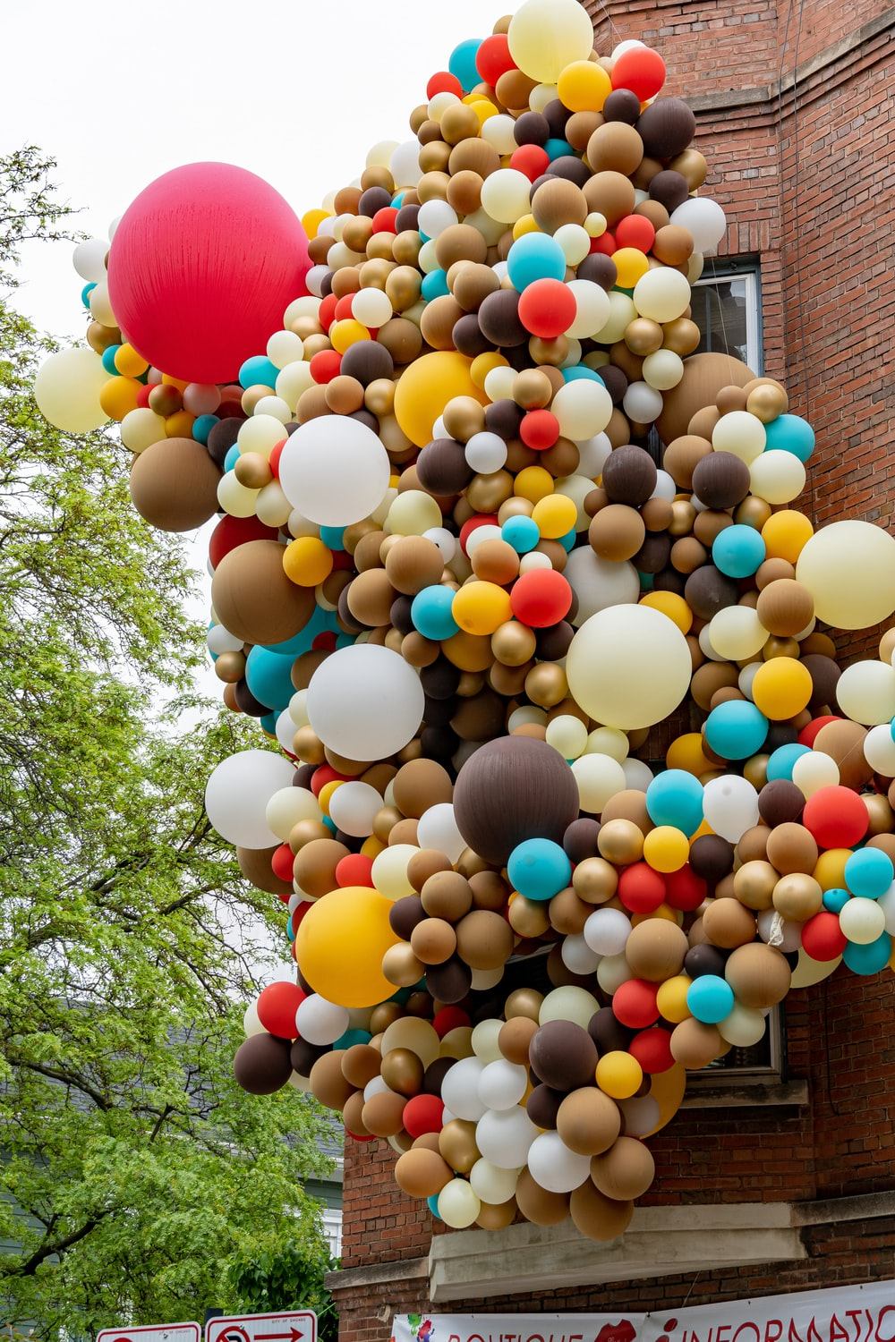balloon lot in brown building near tree during daytime