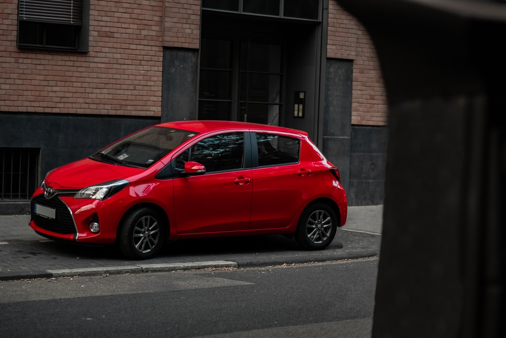 parked red 5-door hatchback beside building