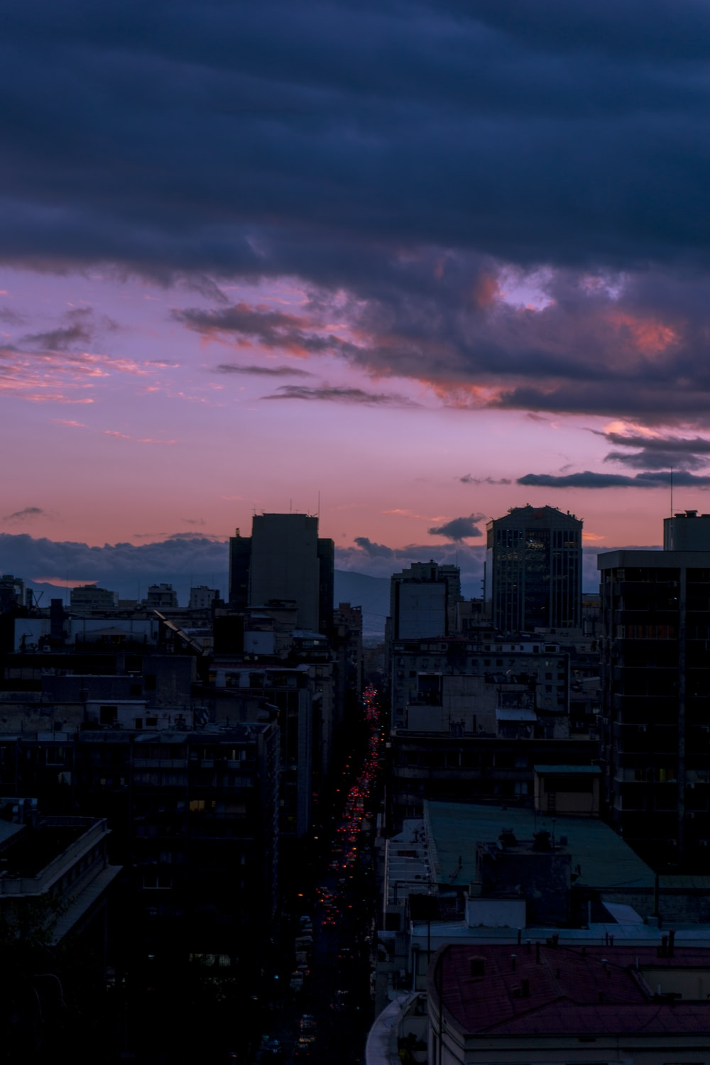 grey clouds looming above the city during sunset