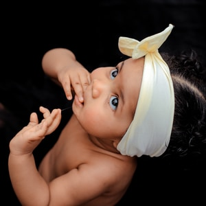 toddler wearing yellow ribbon close-up photography