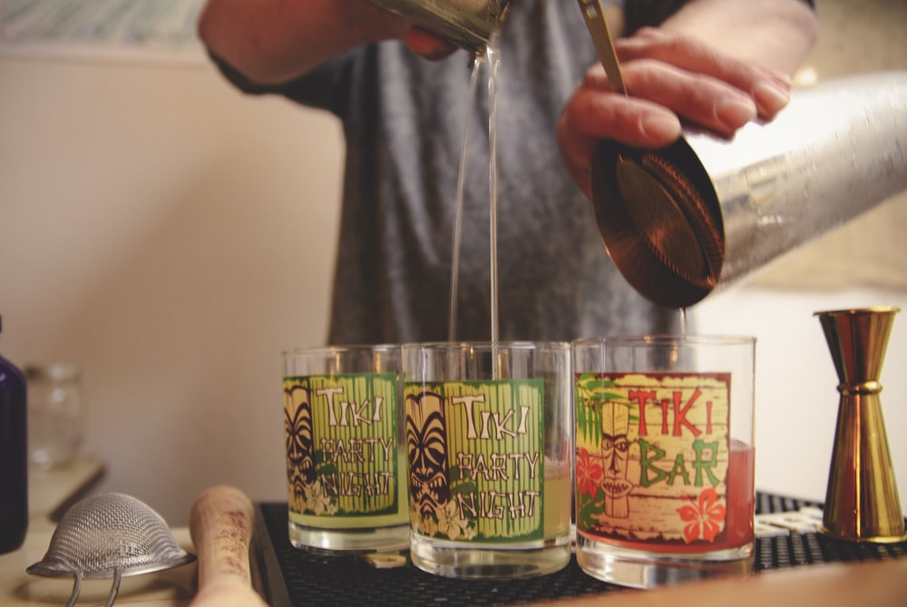 person pouring beverages in three Tiki glasses