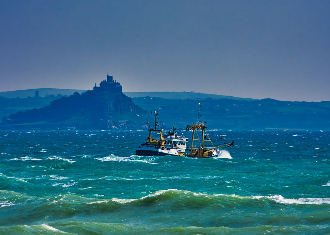 Fishing trawler sailing past St Michael's Mount in Cornwall
