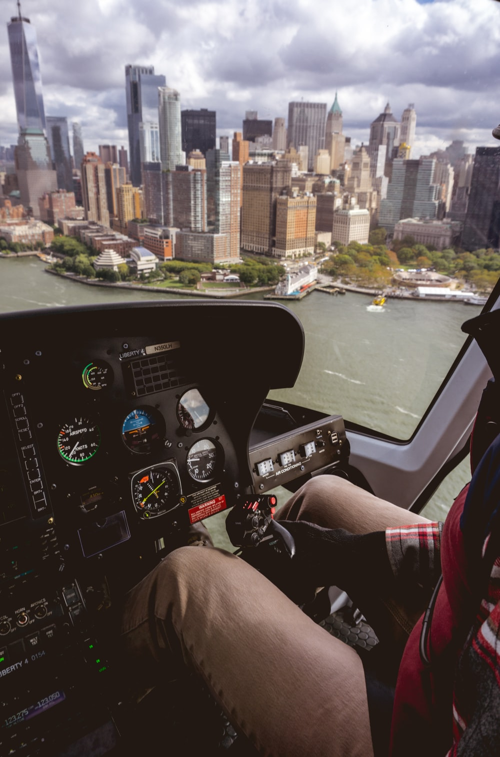 man riding helicopter near buildings