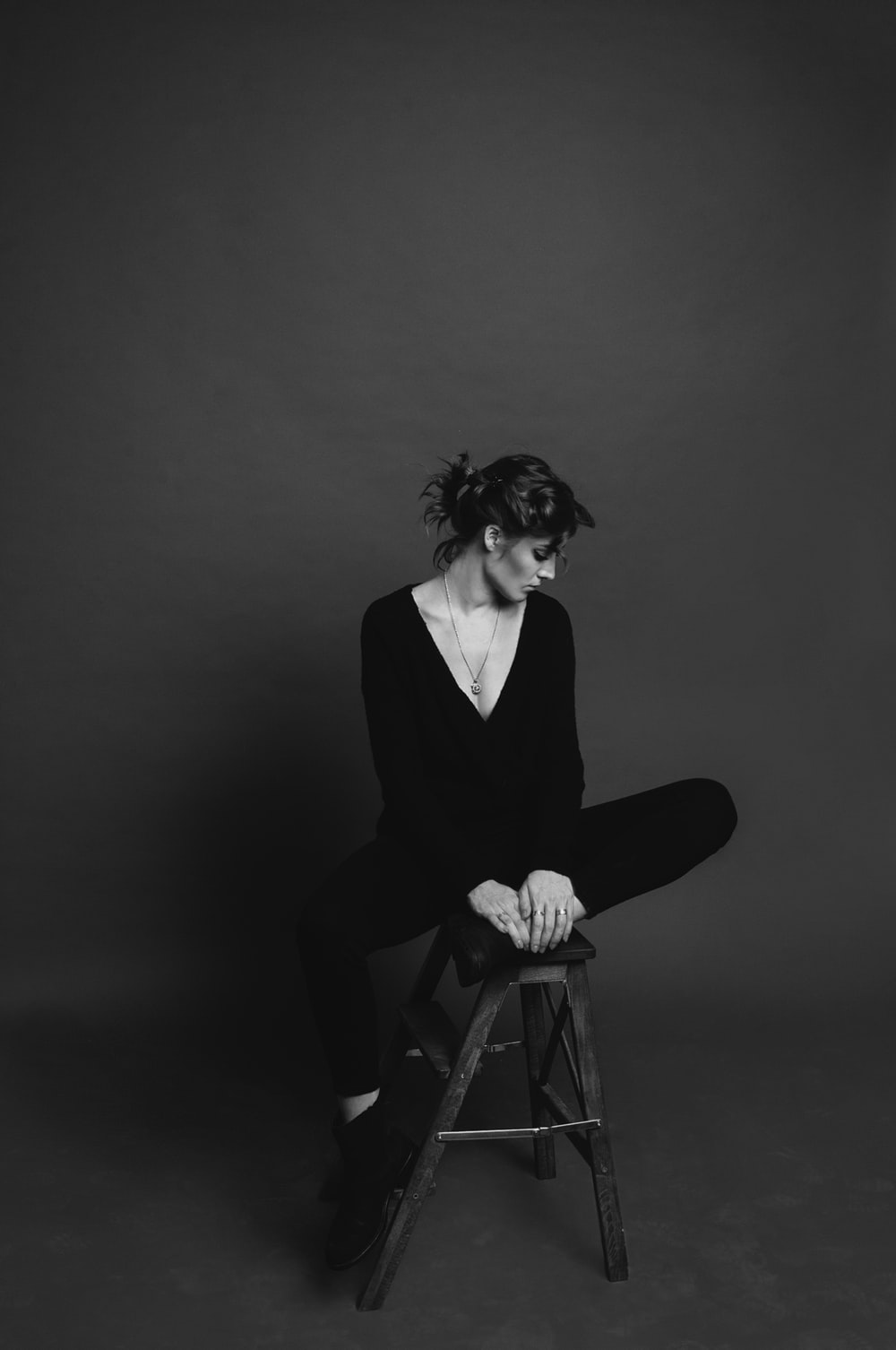 grayscale photo of woman sitting on stool