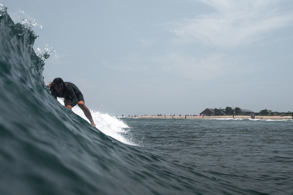 man surfing on focus photography