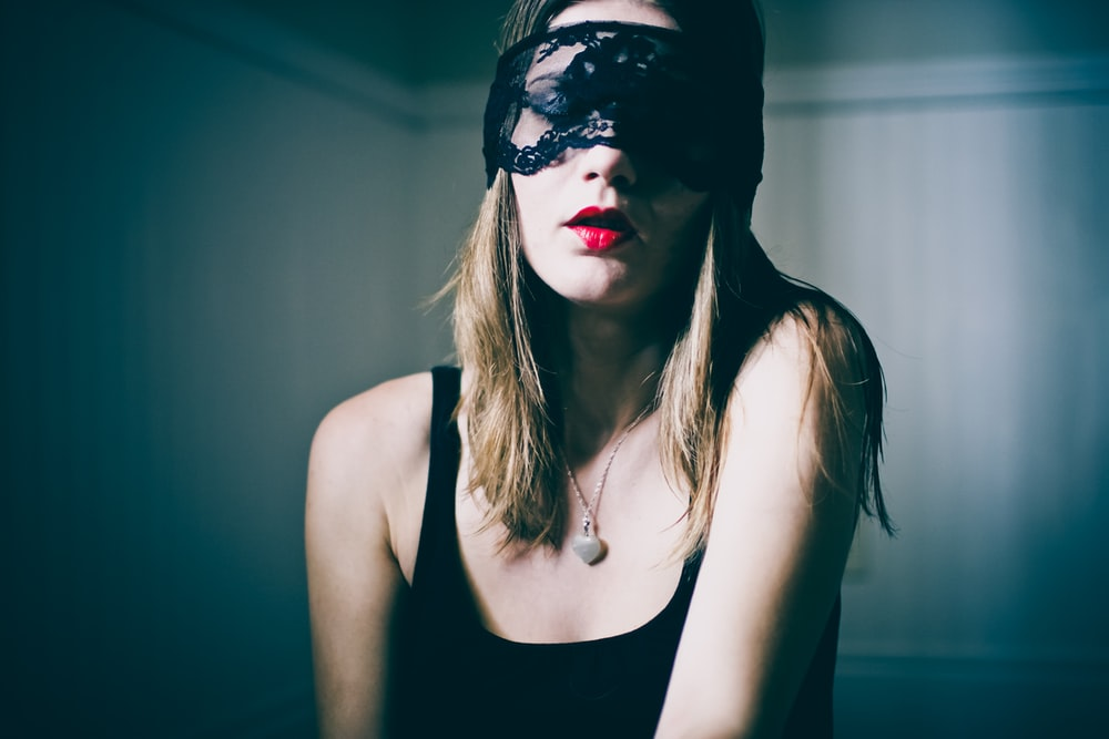 woman wearing black tank top wearing black lace eye mask