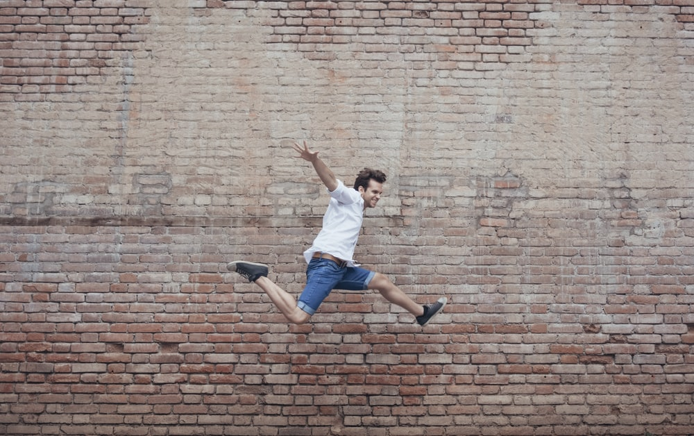 person in white shirt and blue denim jeans jumping beside brown walll