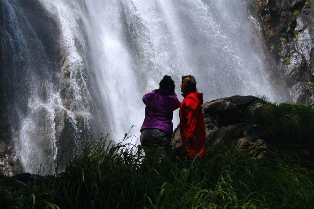 two persons standing on grass looking at the waterfalls