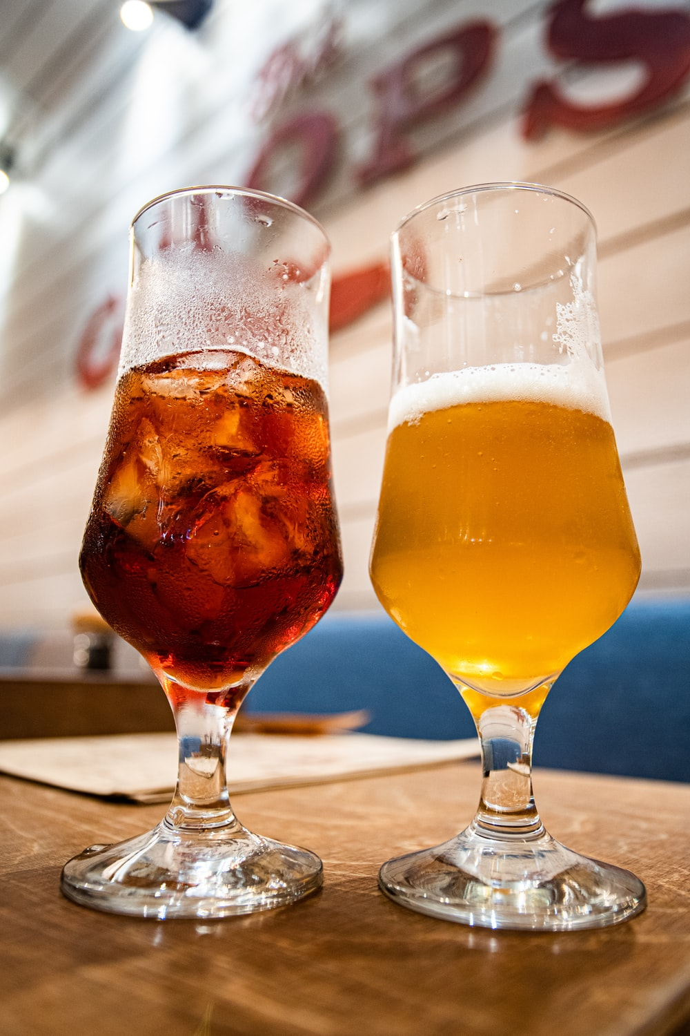 two clear footed glasses filled with beer and tea
