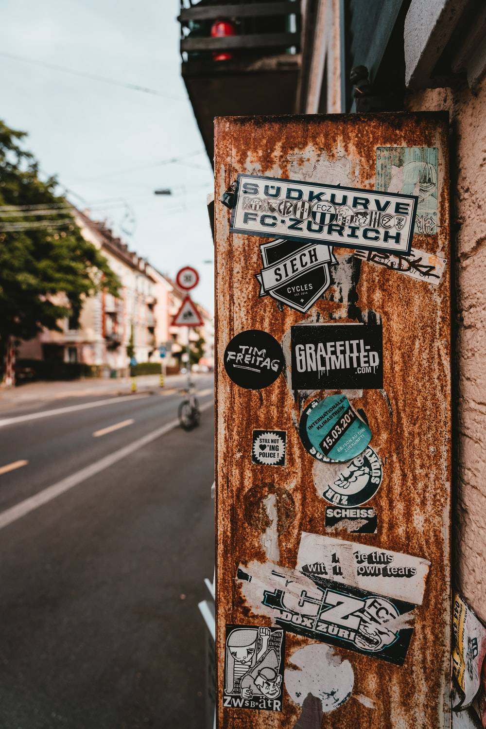 stickers on brown wall beside road during daytime