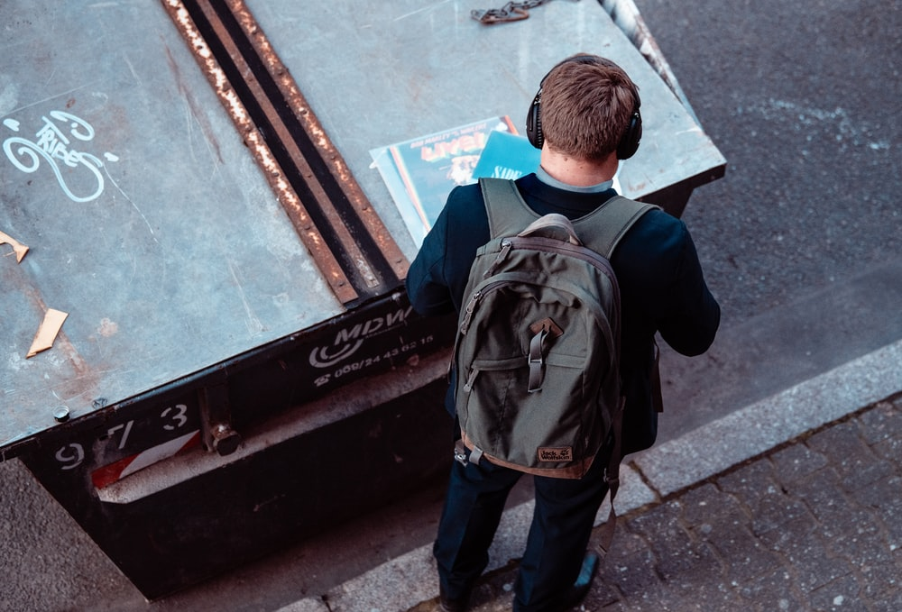 man standing with black backpack