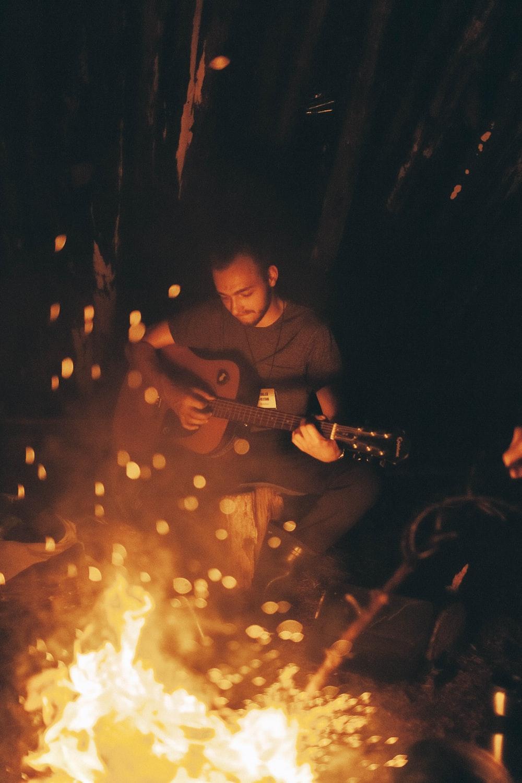 man playing guitar beside bonfire