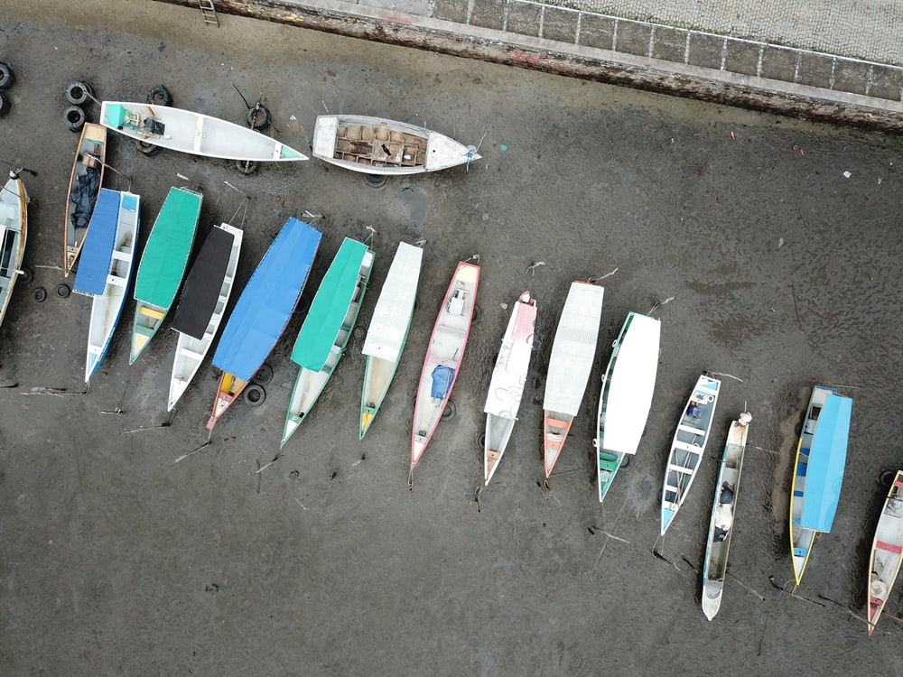 aerial photography of canoes on gray sand