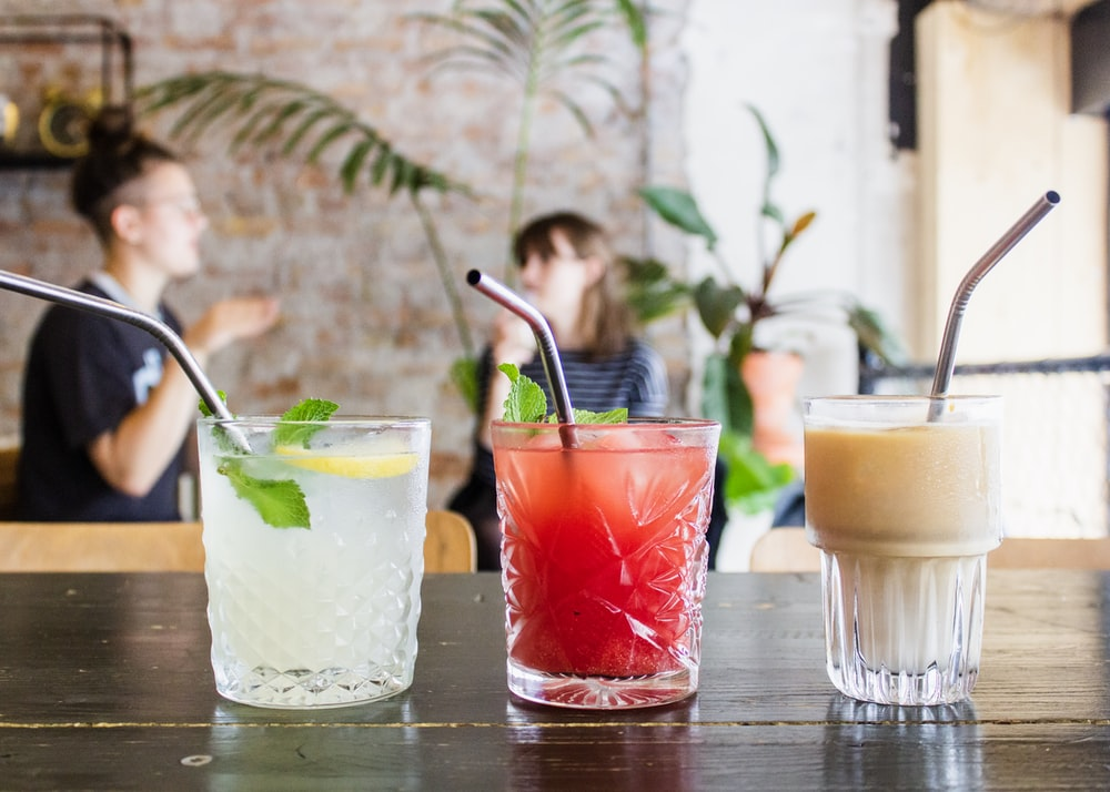 three assorted drinks in glasses with straws