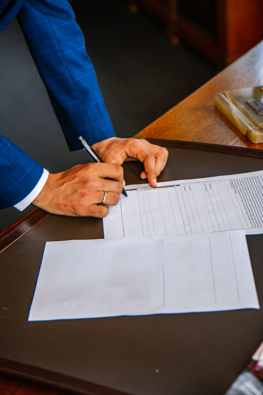 person writing on white form paper