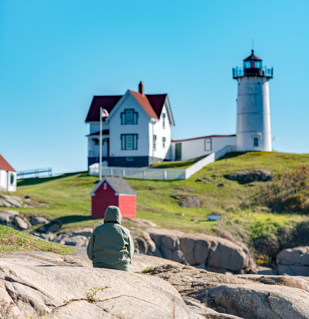 person sitting on rock facing the shed in front of house and USA flag on pole near lighthouse during day