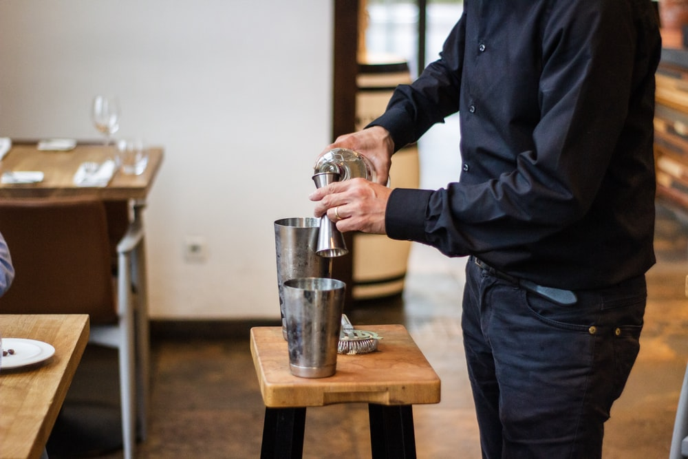 man pouring drink in cup