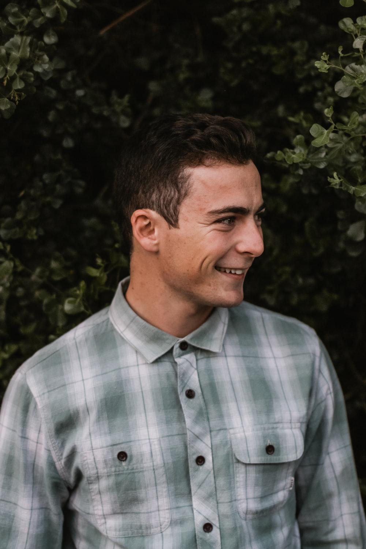smiling man beside bushes
