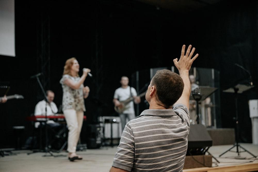 man wearing grey stripe polo shirt raising his right hand