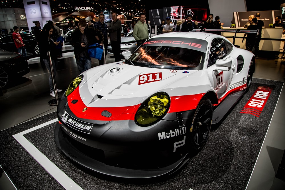 white, red, and grey Porsche 911 RSR on display at car show