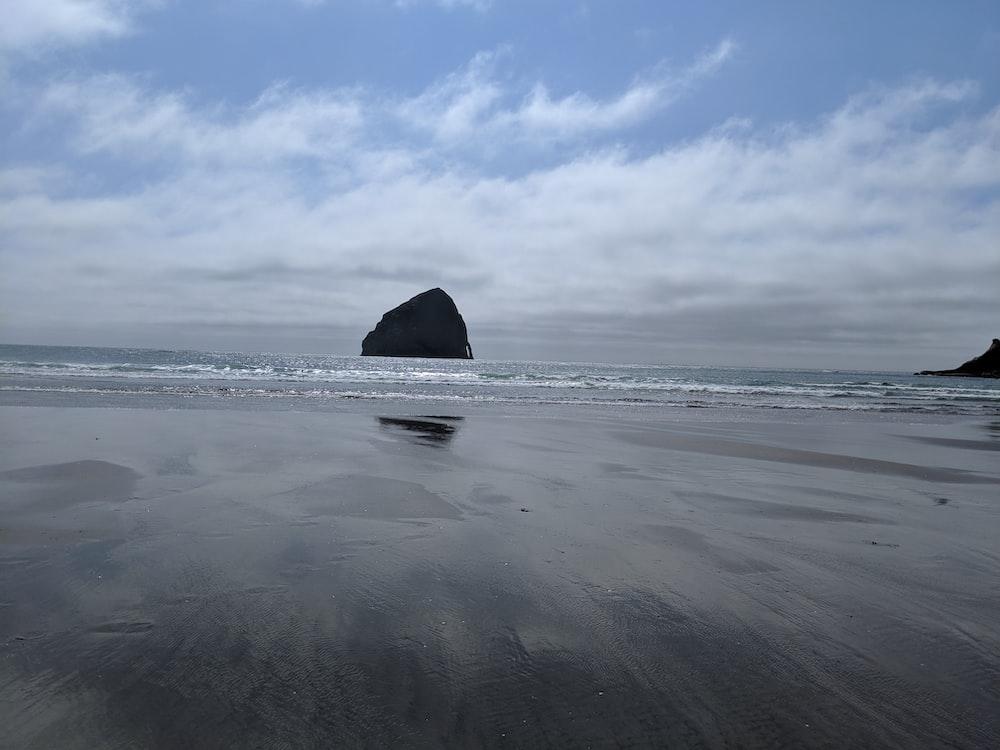black coastal stack during daytime