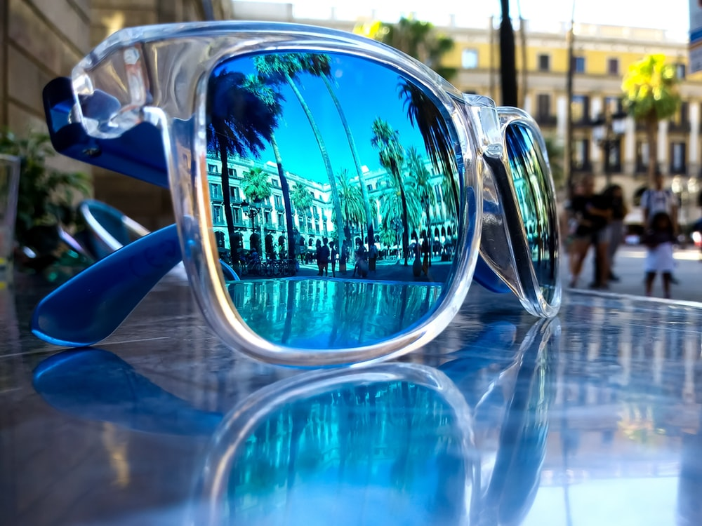 gray and blue framed sunglasses on gray table