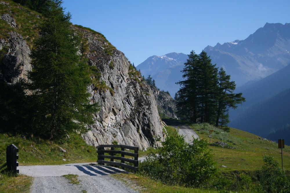 brown wooden bridge handrail besides gray hill