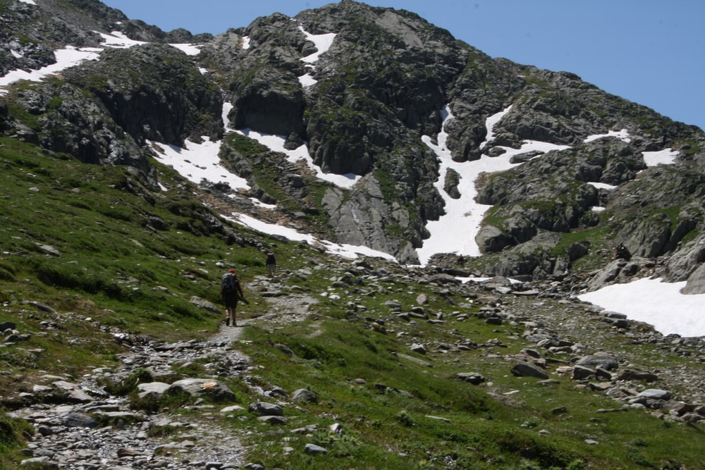 person walking across gray mountain