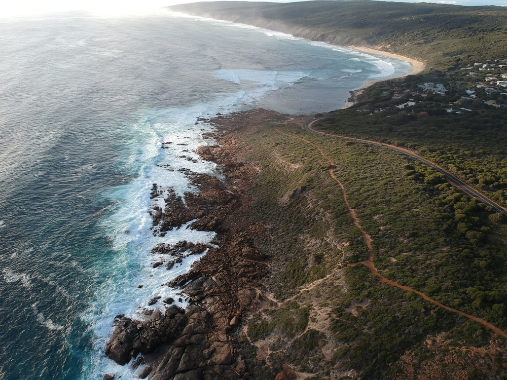aerial photography of open field and seashore during daytime