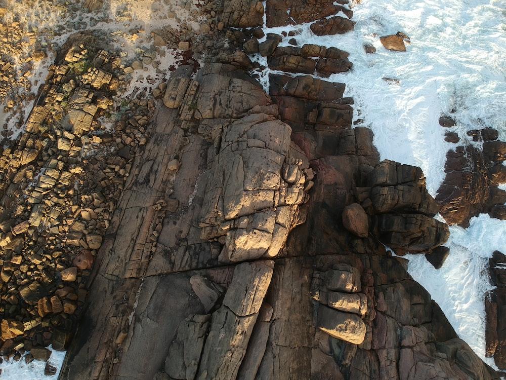 aerial photography of waves crashing on coastal rocks