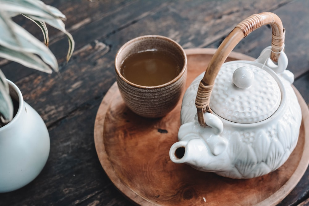 white and brown ceramic teapot on wooden tray