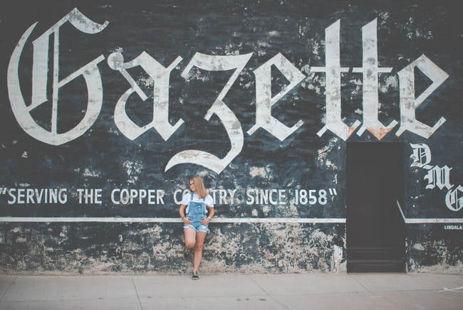 woman standing and leaning on Gazette painted wall during daytime