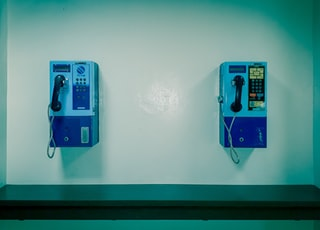two white and blue telephones close-up photography