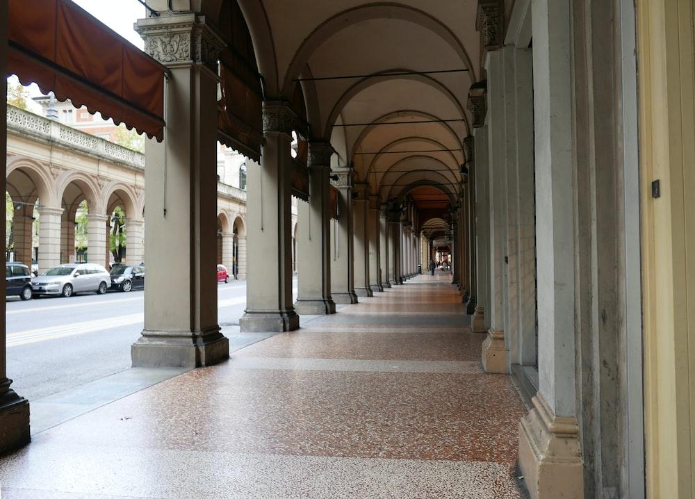 brown tiled hallway beside road during daytime