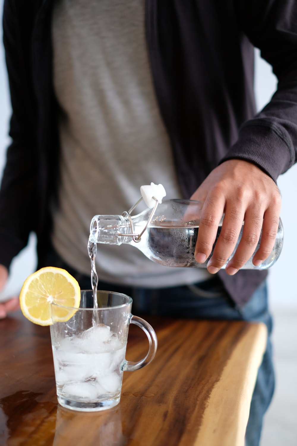 man pouring water in glass