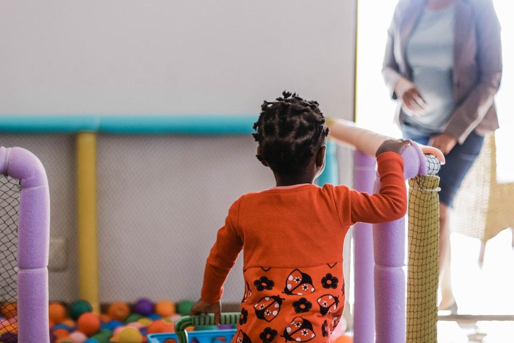 toddler wearing orange long-sleeved shirt carrying plastic basket
