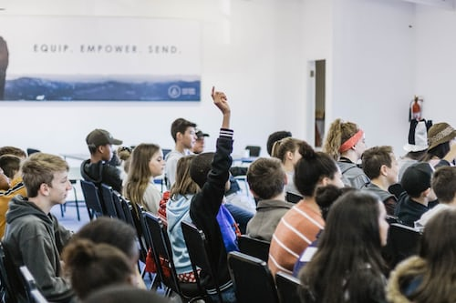 student raising hand for professor