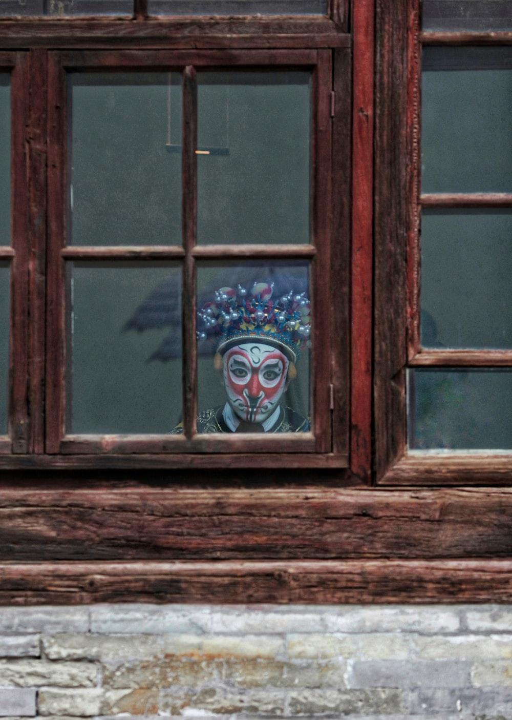 man wearing mask behind glass window