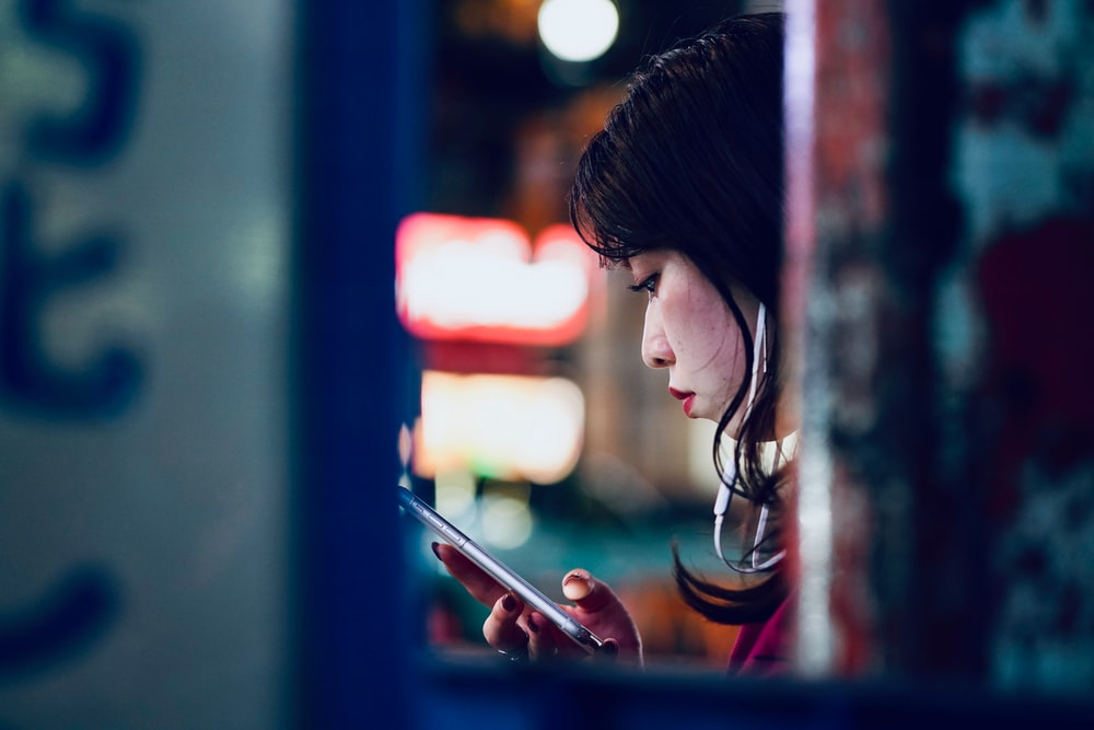 woman holding smartphone on focus photography